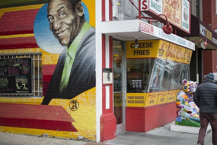A man walks past a mural of comedian Bill Cosby painted on the side of Ben's Chili Bowl in Washington, DC, Dec 4, 2014. The US Navy has revoked Bill Cosby's title of honorary chief petty officer, citing allegations of sexual abuse against the comedia