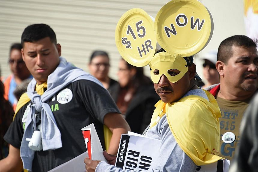 Fast-food workers, health-care workers and their supporters shouting slogans at a rally and marching to demand an increase of the minimum wage to US$15 (S$19.70) an hour, in Los Angeles on Dec 4, 2014. -- PHOTO: AFP