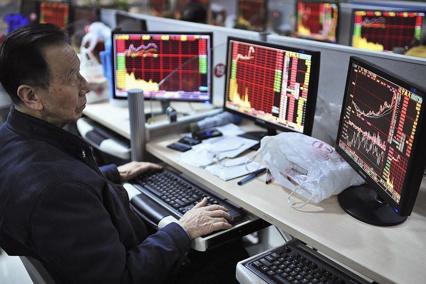 An investor looks at computer screens showing stock information at a brokerage house in Hefei, Anhui province. -- PHOTO: REUTERS