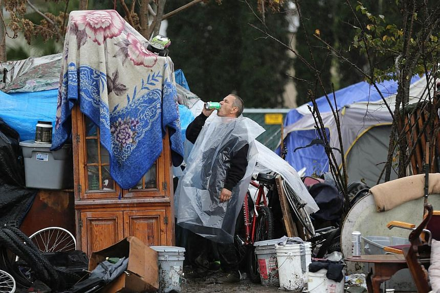"""A man who only goes by the name David gulps down a drink at the Silicon Valley homeless encampment known as """"The Jungle"""" on Wednesday, Dec 3, 2014 in San Jose, California. More than 300 residents of the shantytown have been given notices to leave the"""