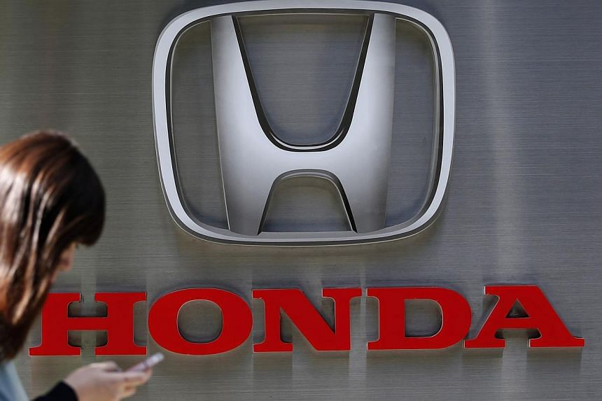 A woman using her mobile phone walks past a logo of Honda Motor Co outside the company's dealership in Tokyo on Oct 28, 2014. -- PHOTO: REUTERS