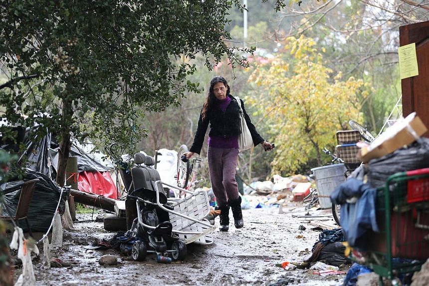 "An unidentified person walks along a muddy path at the Silicon Valley homeless encampment known as ""The Jungle"" on Wednesday, Dec 3, 2014 in San Jose, California. More than 300 residents of the shantytown were given notices to leave the area by the m"