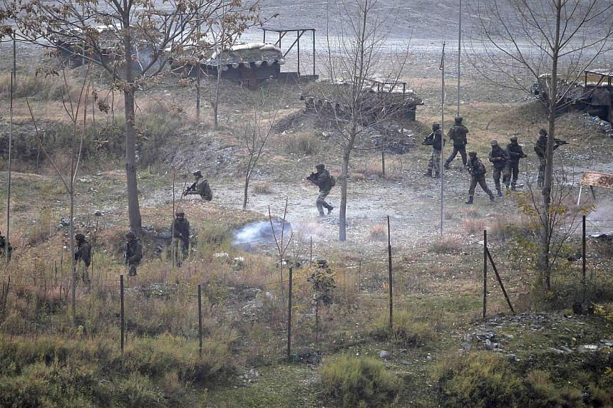 Indian army soldiers search for suspected militants as smoke rises from a bunker after a gunbattle in Mohra in Uri Dec 5, 2014.Militants hurling grenades stormed an army camp in Indian Kashmir on Friday, killing 11 troops and police in a day of