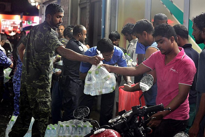 Police officials and security personel distribute bottles of water to residents after a fire at a desalination plant affected water supplies in Male onDec 4, 2014. -- PHOTO: AFP