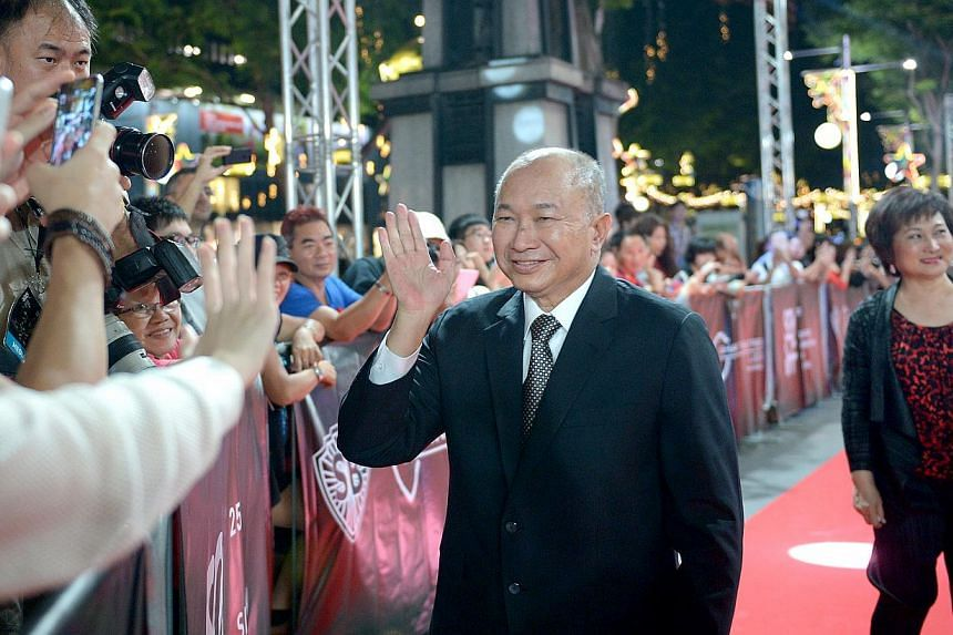 Director John Woo (centre) and his wife Annie Woo (right) arrive at the Singapore International Film Festival at Shaw House on Dec 4, 2014. -- ST PHOTO: LIM SIN THAI