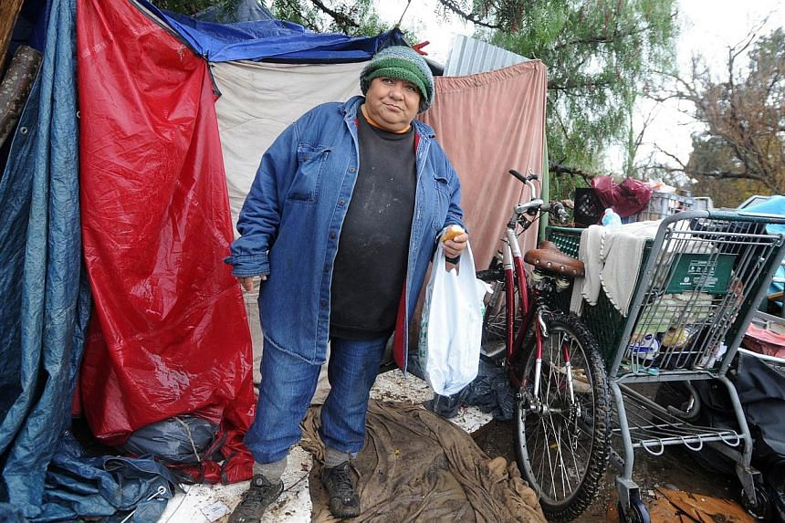 """Grace Hilliard stands outside her tent at a Silicon Valley homeless encampment known as """"The Jungle"""" on Wednesday, Dec 3, 2014 in San Jose, California. More than 300 residents of the shantytown have been given notices to leave the area by the morning"""