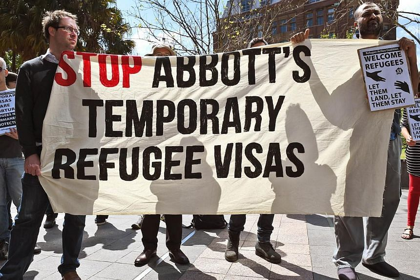 Protesters hold up banners at a rally in Sydney on Sept 26, 2014, opposing Australia's plan to introduce controversial temporary visas for refugees. -- PHOTO: AFP