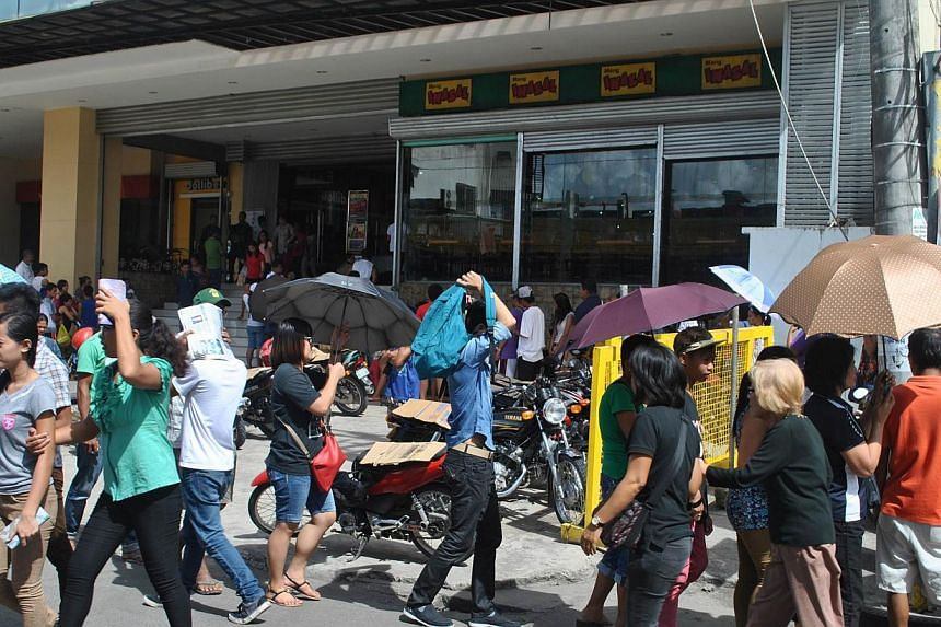 Residents crowd the entrance of a shopping mall to shop for food supplies in Tacloban City, central Philippines on Dec 4, 2014, ahead of the arrival of Typhoon Hagupit on Dec 6. -- PHOTO: AFP