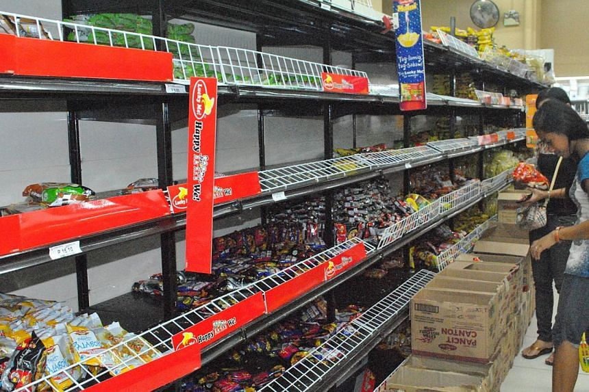Residents stock up on food supplies from a grocery store in the city of Tacloban, central Philippines on Dec 4, 2014, ahead of the landfall of Typhoon Hagupit. -- PHOTO: AFP