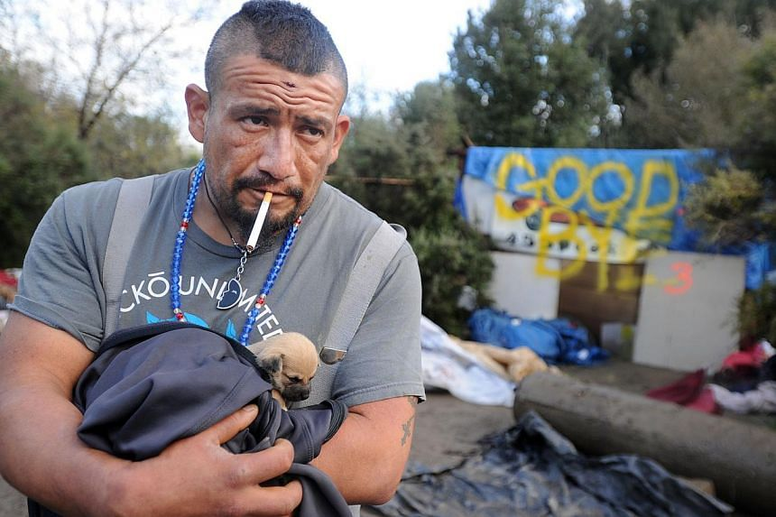 Valentin Cortez, a two-year resident, looks on as a Silicon Valley homeless encampment known as The Jungle is bulldozed on Dec 4, 2014, in San Jose, California. Today, bulldozers, trash trucks and police officers assisted dozens of city contractors a
