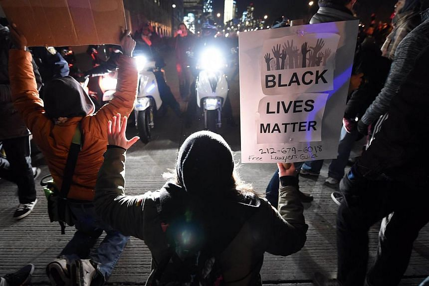 Protesters hold up their hands before police blocking traffic on the West Side Highway during demonstrations Dec 4, 2014 in New York City against the chokehold death of an unarmed black father-of-six by a white police officer. -- PHOTO: AFP