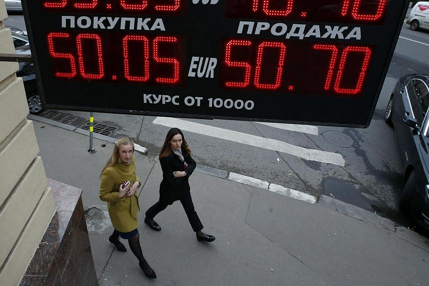 Women walk past a building under a board showing currency exchange rates in Moscow, Oct 7, 2014. Only one top executive in eight at major financial services firms is a woman and the pace of change at banks and other companies is too slow, accord