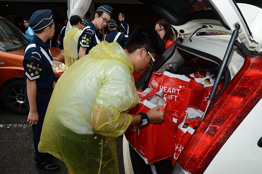 Cadets from The Boys' Brigade loading the food hampers into the volunteers' cars. -- PHOTO: BOYS' BRIGADE