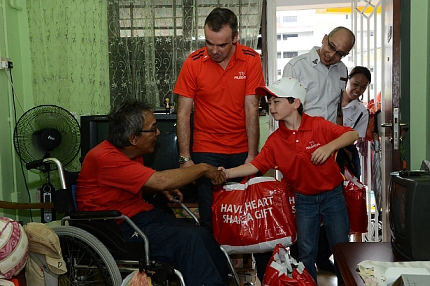 Mr Kahllid Selamat receives his food hampers from Mr Sandham, his son Mikey and Mr Tan. -- PHOTO: BOYS' BRIGADE