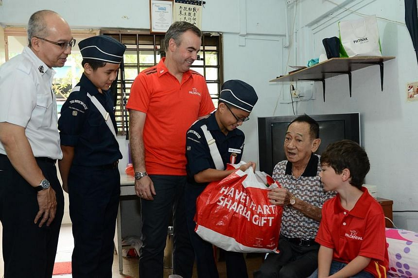 Mr Sim Soo Hee receives the food hampers from Mr Tan, Mr Sandham, his son Mikey and cadets from The Boys' Brigade. -- PHOTO: BOYS' BRIGADE
