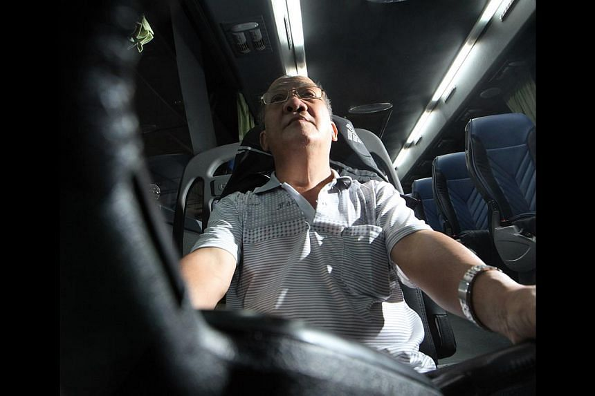 """Mr Lee Kim Huat has downsized from driving a 40- to a 19-seater coach. """"My life is very simple. Driving is the only job that I have learnt to do,"""" he says. -- ST PHOTO: NEO XIAOBIN"""