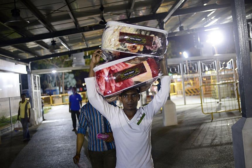 A worker from Bangladesh with a load of blankets at the bus terminal in Tekka Lane. About 200 buses call at the station from 2pm to 9pm on Sundays. -- ST PHOTO: MARK CHEONG