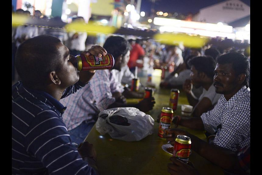 A foreign worker downing a can of beer at a beer garden in Chander Road. The cordon tape behind him was put up in recent months to mark the boundary between the no-alcohol zone and the area where people can consume alcohol, and is now a common sight