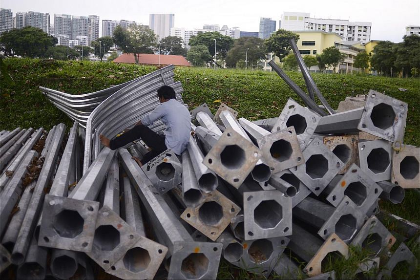 A worker finding privacy to make a phone call among a stack of lamp posts in a field in Race Course Road. Others go there to watch cricket matches. -- ST PHOTO: MARK CHEONG