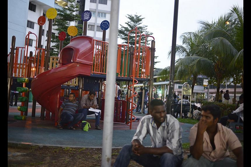 Workers hanging out at the playground at Block 661, Buffalo Road. One worker said there has been a decline in the number of workers in the area on weekends. -- ST PHOTO: MARK CHEONG