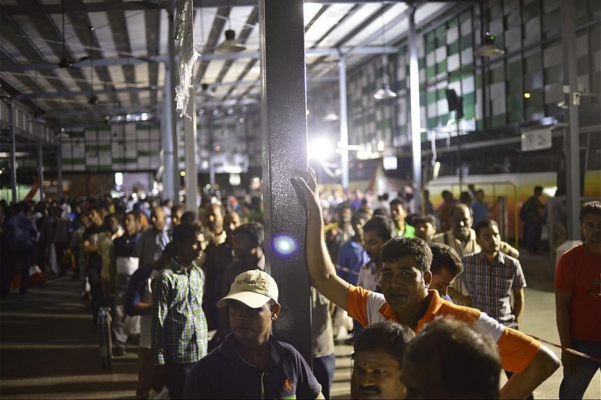 Foreign workers lining up to board a shuttle bus at the newly built bus terminal in Tekka Lane. Initiated by the Land Transport Authority, the bus station is fenced up and closes at 9pm, when the last shuttle bus leaves to the various dormitories. --