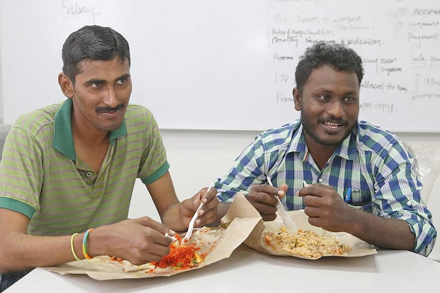 Construction workers Palaniyappan Sakthivel (left) and Natarajan Muruganandam tucking into their supper while being interviewed by Insight. Mr Palaniyappan is helping build Mediapolis@one-north in Buona Vista and Mr Muruganandam is working on the Tho