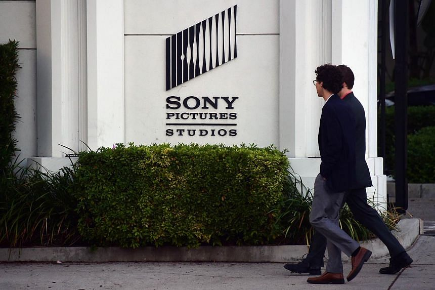 Pedestrians walk past an exterior wall to Sony Pictures Studios in Los Angeles, California on Dec 4, 2014. -- PHOTO: AFP