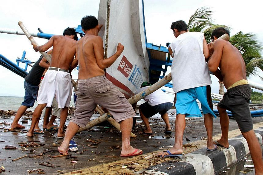 Fishermen carry their outrigger to higher ground in Legazpi City, south of Manila on Dec 5, 2014, ahead of the landfall of Typhoon Hagupit. -- PHOTO: AFP