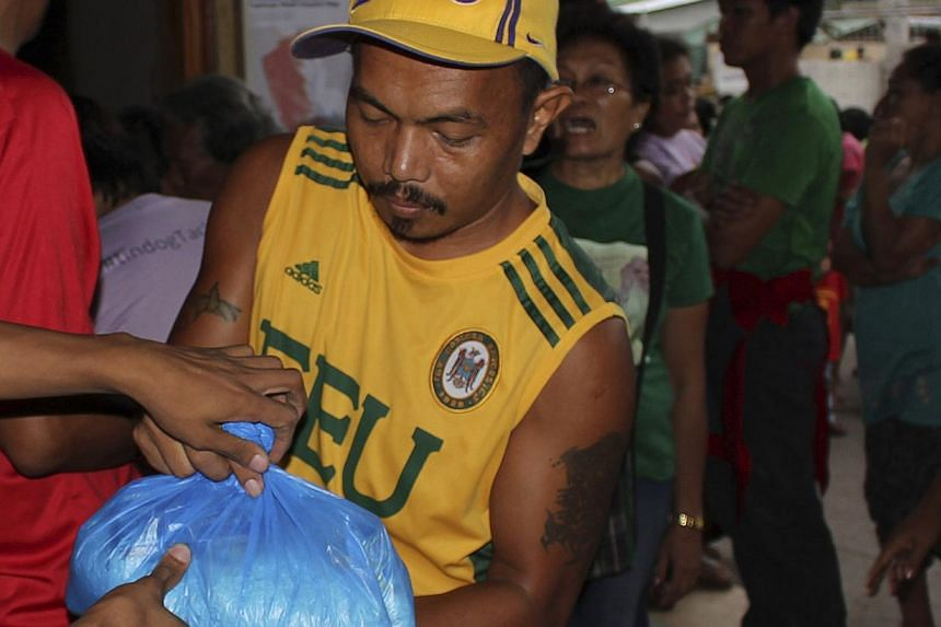 An evacuee receives relief goods after evacuating due to super-typhoon Hagupit in Tacloban city, central Philippines, on Dec 5, 2014. -- PHOTO: REUTERS