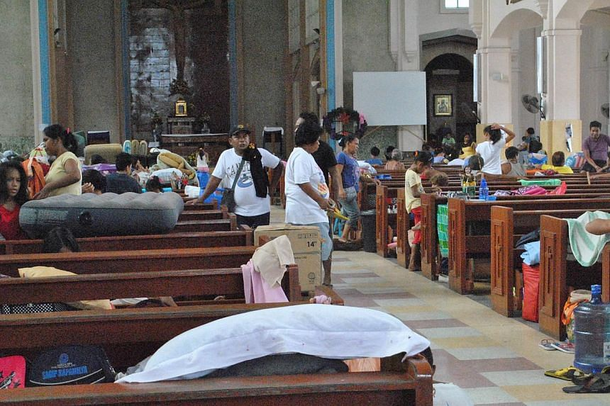 Residents take shelter inside a church in Tacloban City, central Philippines, on Dec 5, 2014, ahead of Typhoon Hagupit making landfall. -- PHOTO: AFP