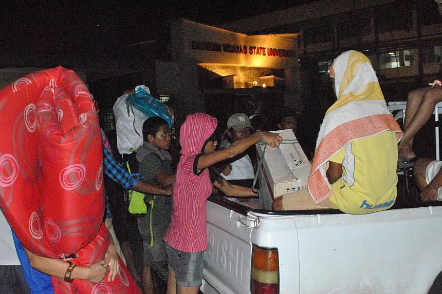 Residents arrive on a vehicle with their beloingings at an evacuation center in Tacloban City, central Philippines, on Dec 5, 2014, ahead of the landfall of Typhoon Hagupit. -- PHOTO: AFP