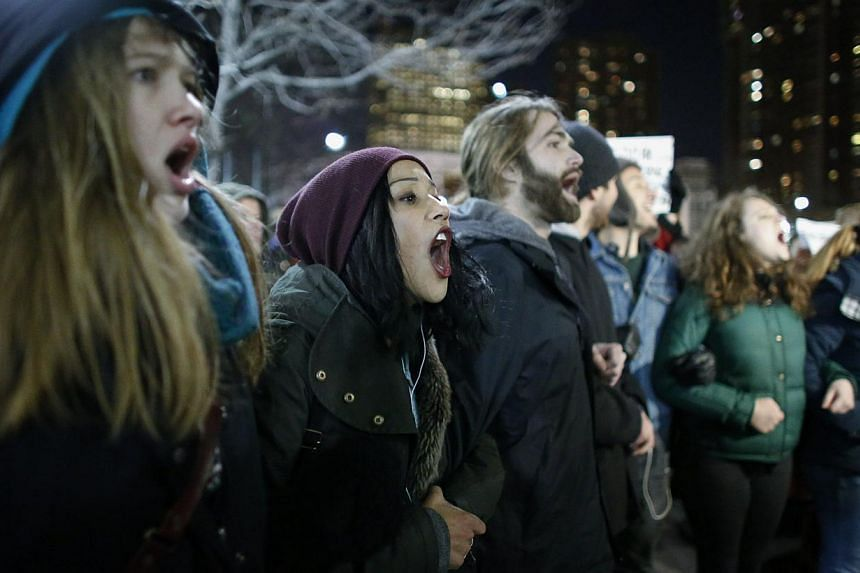Demonstrators block a street during a protest following the decision by a Staten Island grand jury not to indict a police officer who used a chokehold in the death of Eric Garner in July, on Dec 4, 2014 in New York City. -- PHOTO: AFP