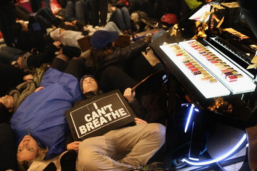 """Demonstrators stage a """"die-in"""" next to a lipstick display inside the iconic Macy's department store in Midtown Manhattan on Dec 5, 2014 in New York City. -- PHOTO: AFP"""