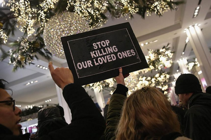 "Demonstrators march through Macy's before staging a ""die-in"" at the iconic department store in Midtown Manhattan on Dec 5, 2014 in New York City. -- PHOTO: AFP"