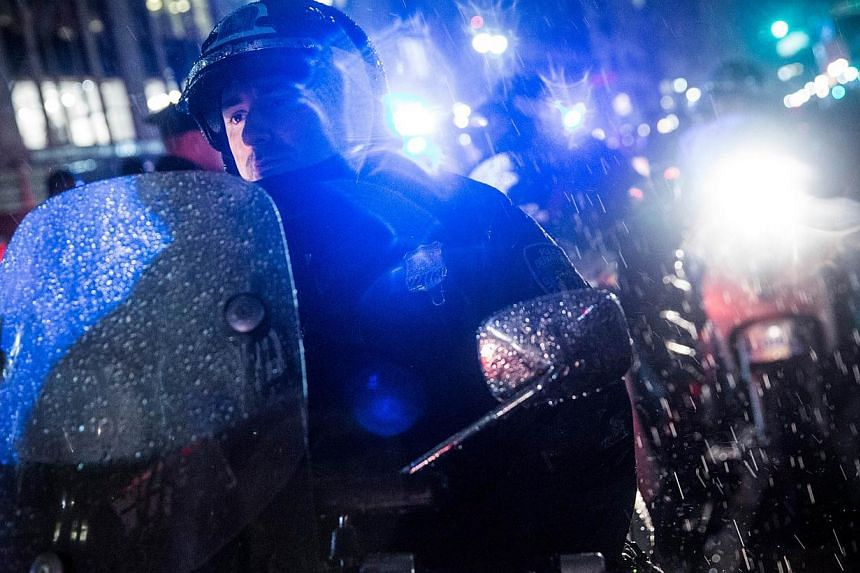 Police monitor demonstrators protesting the Staten Island, New York grand jury's decision not to indict a police officer involved in the chokehold death of Eric Garner in July on Dec 5, 2014 in New York City. -- PHOTO: AFP