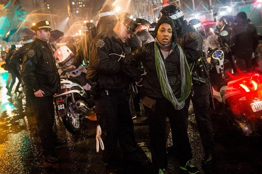 A woman is arrested by police while protesting the Staten Island, New York grand jury's decision not to indict a police officer involved in the chokehold death of Eric Garner in July on Dec 5, 2014 in New York City. -- PHOTO: AFP
