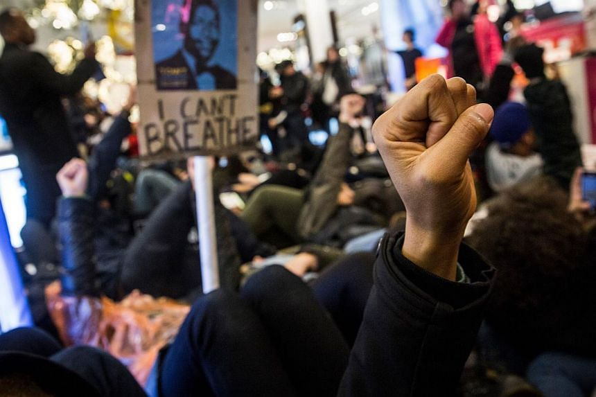 Demonstrators hold a die-in in Macy's on 34th Street protesting the Staten Island, New York grand jury's decision not to indict a police officer involved in the chokehold death of Eric Garner in July on Dec 5, 2014 in New York City. -- PHOTO: AFP