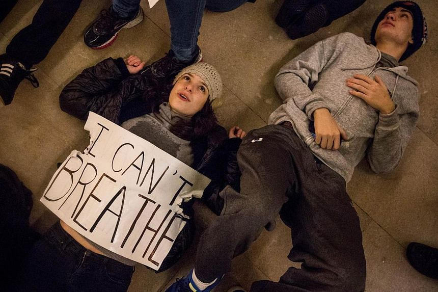 Demonstrators hold a die-in in Grand Central Terminal protesting the Staten Island, New York grand jury's decision not to indict a police officer involved in the chokehold death of Eric Garner in July on Dec 5, 2014 in New York City. -- PHOTO: AFP