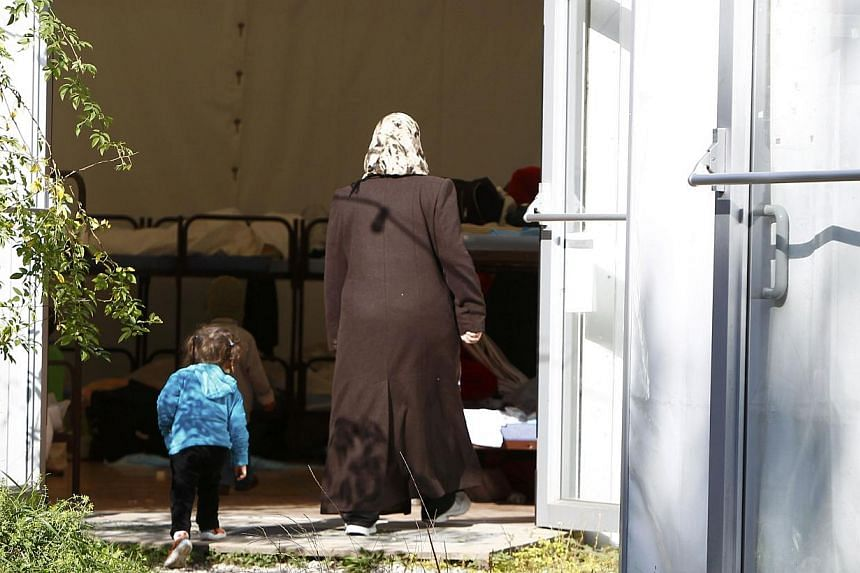 "An asylum seeker and a child enter a refugee tent camp called ""The Tent"" in Munich Oct 10, 2014. Germany expects 230,000 asylum seekers in 2015, which would mean another jump in new arrivals for a country already struggling to handle its load of"