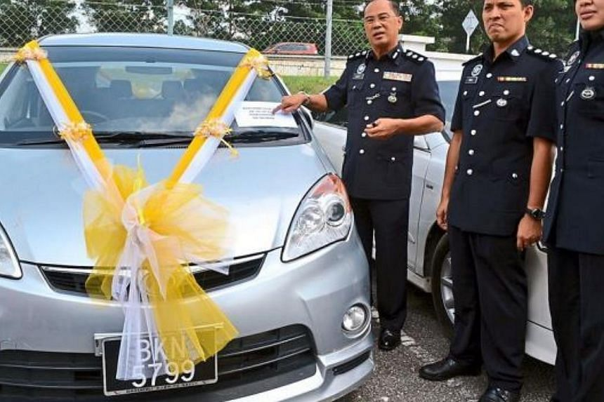 Selangor's Sepang police chief Mohd Yusoff (left) along with other police personnel showing the decorated vehicle that was seized during a raid. -- PHOTO: THE STAR/ASIA NEWS NETWORK