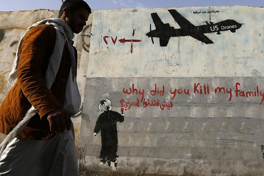A man walks past a graffiti, denouncing strikes by U.S. drones in Yemen, painted on a wall in Sanaa on Nov 13, 2014. -- PHOTO: REUTERS