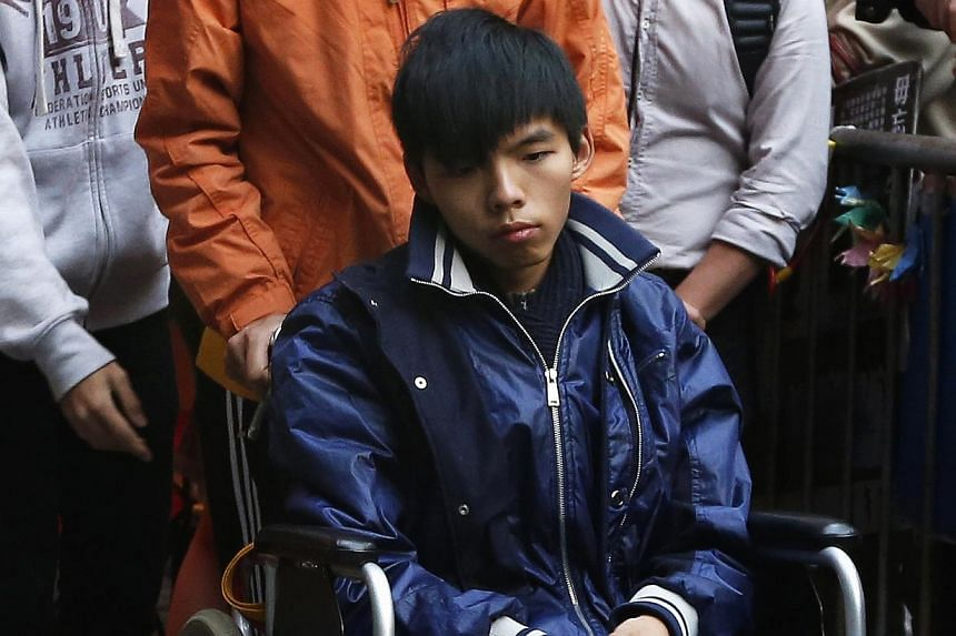 Student leader Joshua Wong, who has undergone more than 90 hours on a hunger strike, sits in a wheelchair as he meets journalists outside the government headquarters in Hong Kong on Dec 5, 2014. -- PHOTO: REUTERS