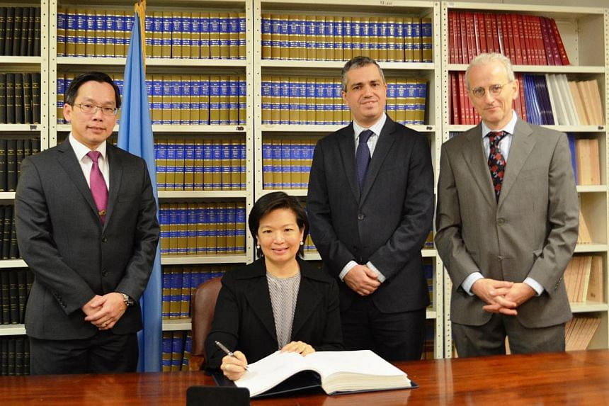 The Permanent Representative of Singapore to the United Nations, Ms Karen Tan (seated), signing the Arms Trade Treaty at the UN Office of Legal Affairs. -- PHOTO: MINDEF