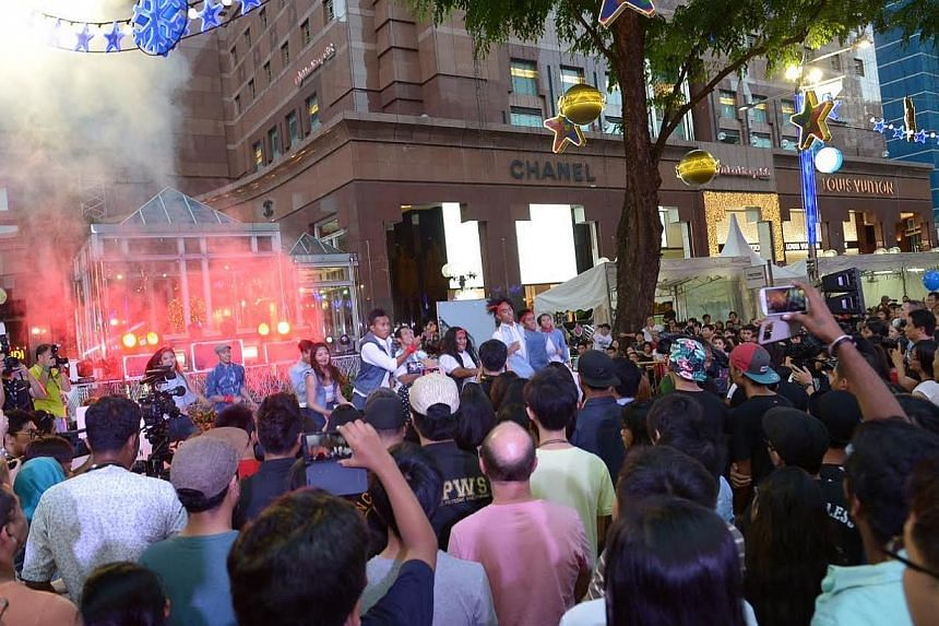 People watch a performance at the third Pedestrian Night at Orchard Road. -- ST PHOTO: DESMOND WEE