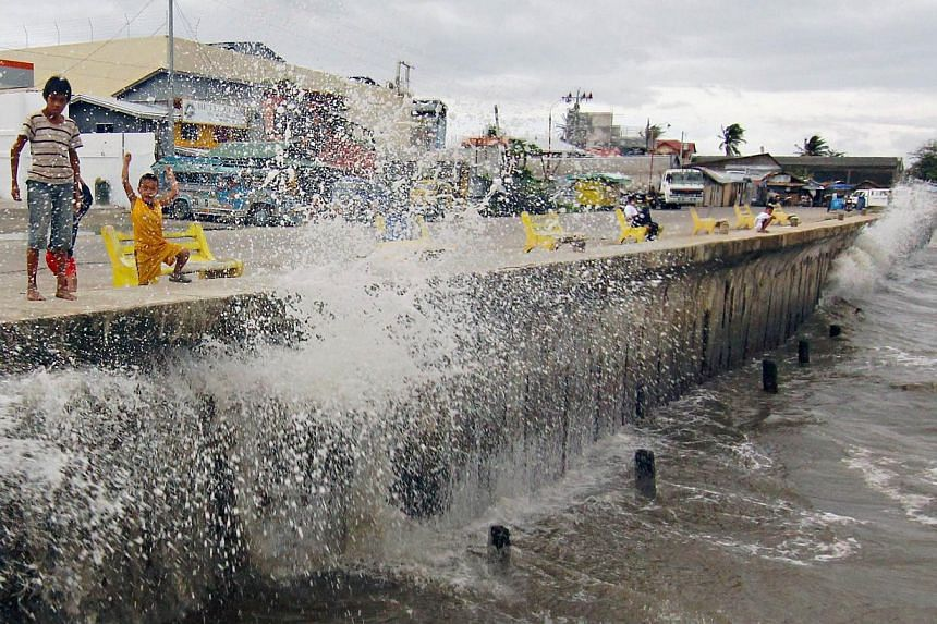 Waves, brought by Typhoon Hagupit, hit the concrete barrier along the Boulevard Seaport in Surigao City in the southern Philippines on Dec 6, 2014. -- PHOTO: REUTERS