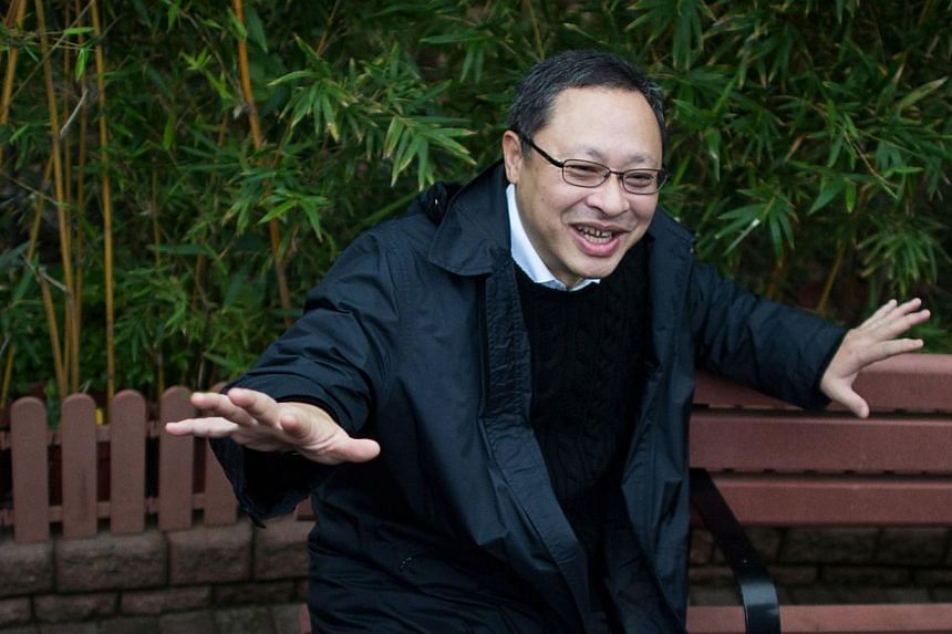 Dr Benny Tai (left), an original founder of the pro-democracy Occupy movement, gestures as he sits on a bench after leaving the police station in Hong Kong on Dec 3, 2014.-- PHOTO: AFP