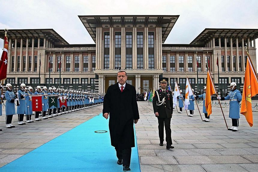 Turkish President Recep Tayyip Erdogan (middle) walks to welcome Russian President Vladimir Putin (unseen) during the official welcoming ceremony at Turkey's Presidential Palace in Ankara on Dec 01, 2014. -- PHOTO: AFP