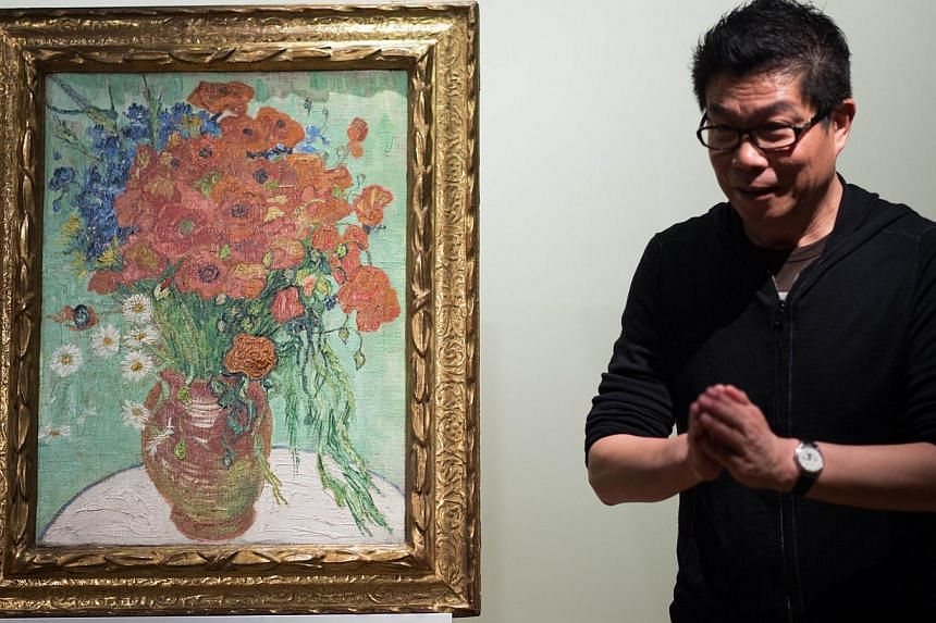 Wang Zhongjun, chairman of the high-powered Huayi Brothers film studio, stands next to his Vincent van Gogh 1890 still life painting Still Life, Vase With Daisies And Poppies, at Sotheby's Hong Kong Gallery in Hong Kong on Dec 6, 2014. -- PHOTO: AFP