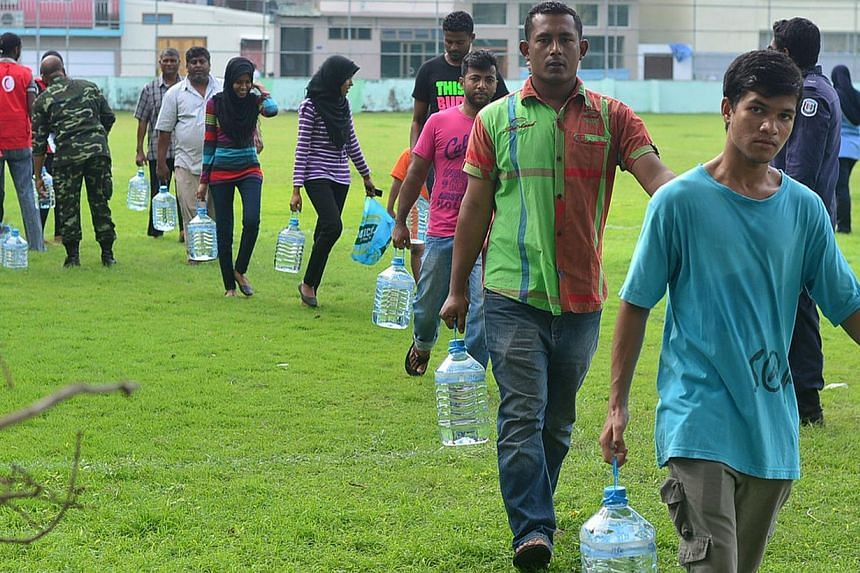 Maldives residents carry their supply of water distributed by Red Crescent and security personnel after a fire at a desalination plant affected water supplies in Male, on Dec 5, 2014. Drinking water had to be airlifted into the Maldivian capital Dec
