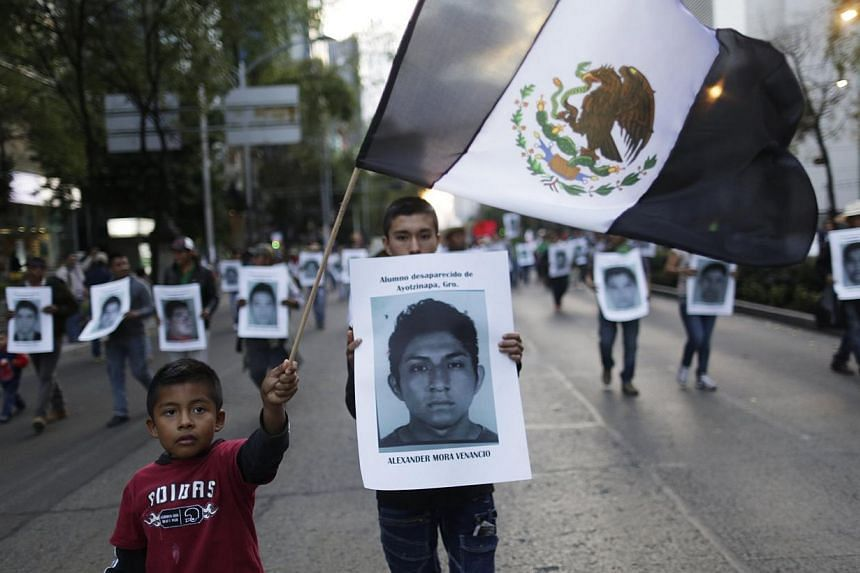 A demonstrator carries a photograph of Alexander Mora Venancio, one of the 43 missing trainee teachers, as a boy waves a Mexican flag with its green and the red parts replaced with black as a sign of mourning, during a march in support of the student